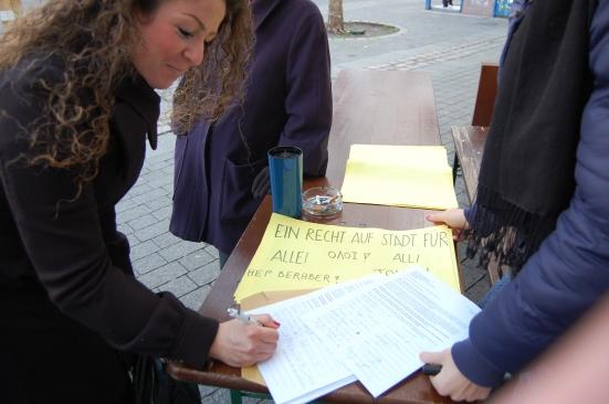Eine GSW-Mieterin unterschreibt den Protestbrief, der einen möglichen Mieterhöhungsstreik ankündigt. Binnen eines Tages haben 170 Haushalte unterschrieben.